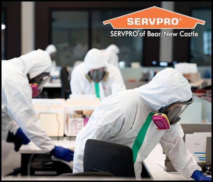 SERVPRO professional in Personal Protection Equipment cleaning and disinfecting a commercial property