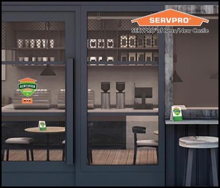 Café store front with Certified: SERVPRO Cleaned decal logo on glass door