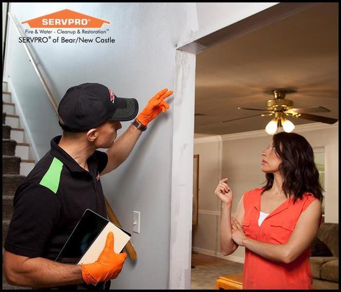 SERVPRO fire damage specialist assessing a fire damage with a customer